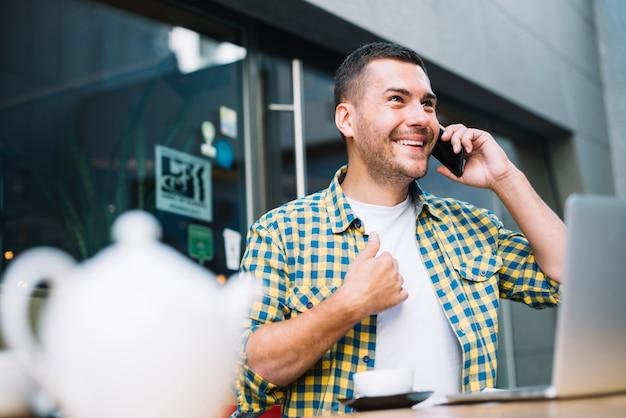 Человек, эмоционально говоря по телефону в кафе