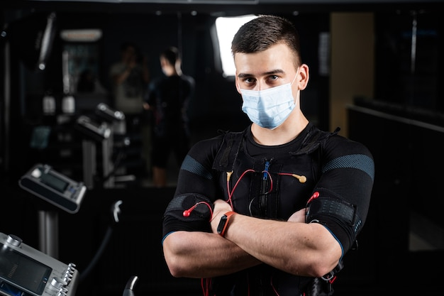 Man in ems suit and medical mask in gym