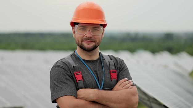 태양광 발전소에 서 있는 동안 제복을 입은 남자 에너지 기술자. 카메라를 보고 있는 동안 팔을 건너는 보호용 헬멧을 쓴 남성 엔지니어의 초상화.
