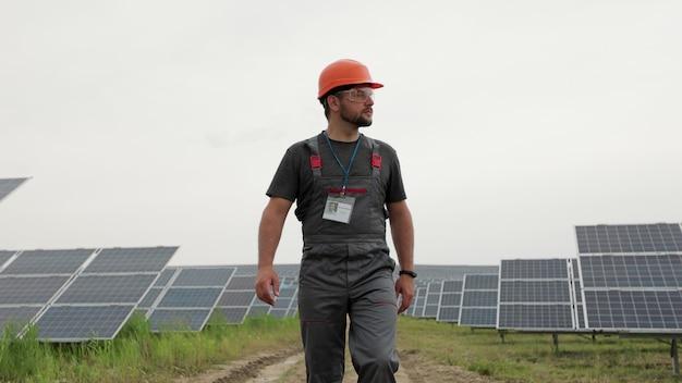 남자 에너지 기술자는 태양 전지판 분야를 걷고 광전지 지상 기반 태양 전지판을 검사합니다. concept.renewable 에너지, 기술, 녹색, 미래.