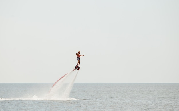 A man engaged in flyboarding on the ocean.