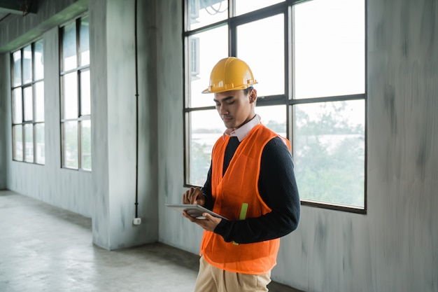 Man engineer hold tablet wearing hardhat and veils