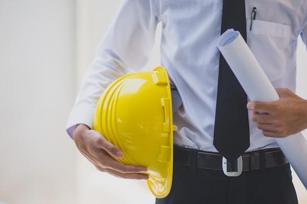 Man engineer holding helmet hard hat work construction building