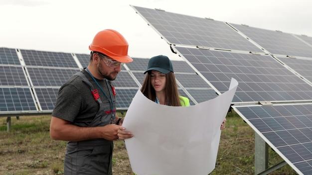 안전모를 쓴 남자 엔지니어와 태양 전지판의 종이 계획 건설을 배우는 검사관 엔지니어 여성. 대체 에너지. 녹색 에너지의 개념입니다.