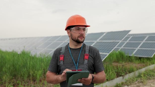 제복을 입은 남자 엔지니어는 디지털 태블릿을 들고 태양 전지판 발전소 근처에서 일합니다. 태양광 패널 분야. 청정 에너지 생산. 친환경 에너지.
