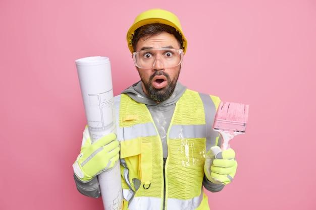 男性エンジニアは、再建後に新しい家の壁をペイントするために、作業服を着た多くの仕事をしていることにショックを受けた建築ツールの青写真でポーズをとります。アパートの改善