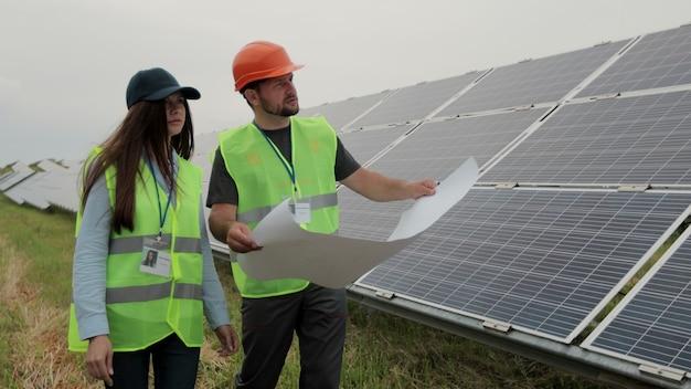 태양 전지 패널 근처 종이 다이어그램에 여성 검사 개체를 보여주는 남자 엔지니어. 대체 에너지. 녹색 에너지의 개념입니다.