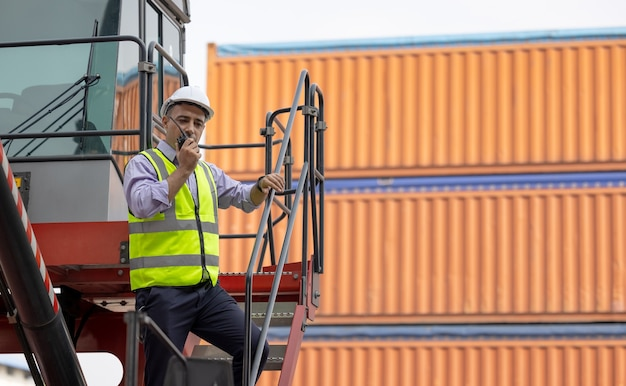 出荷ヤードでトランシーバーを使用する男性エンジニアである産業労働者は、輸出入ビジネスでトランシーバーによるコンテナの積み込みを管理しています。