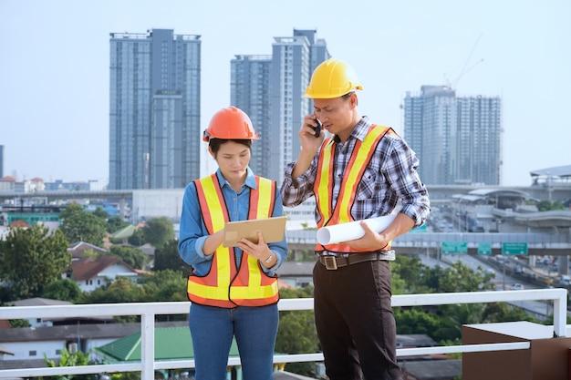 エンジニアは高層ビルに立つ