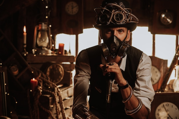 Man of engineers in a steampunk suit with a top hat with glasses and a gas mask