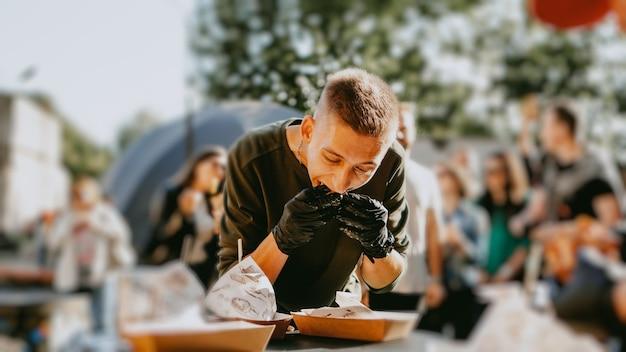 Мужчина наслаждается фестивалем уличной еды, пивом и бургерами. бургер битва