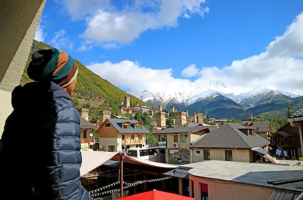 Человек наслаждается прекрасным видом на город местия со сванскими башнями и кавказские горы, грузия