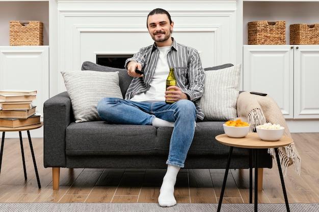 ビールを楽しんで、ソファに座ってテレビを見ている男
