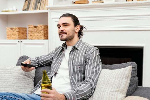 ビールを楽しんでテレビを見ている男