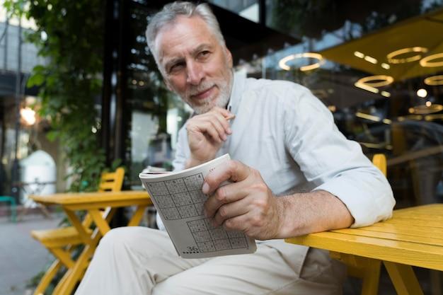 종이 위에서 스도쿠 게임을 즐기는 남자