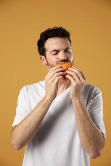 L'uomo si diverte a mangiare un hamburger