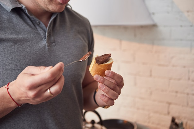 Man enjoying eating chocolate paste spreading nut butter on ciabatta slice