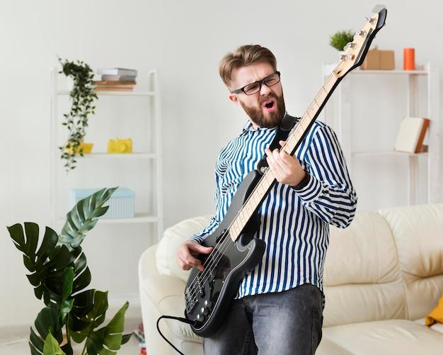 自宅でエレクトリックギターを楽しむ男