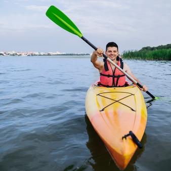 Man enjoying the kayaking on idyllic lake