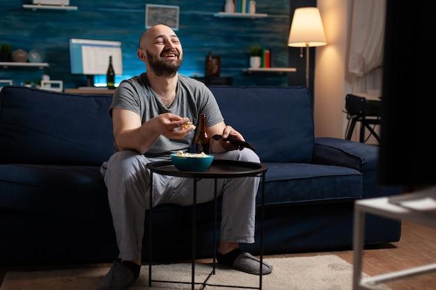 Uomo che si diverte a rilassarsi guardando le serie di commedie televisive a casa