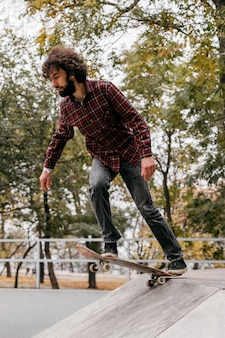 都市公園でスケートボードを楽しんでいる男