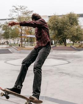 都市公園で屋外スケートボードを楽しんでいる男