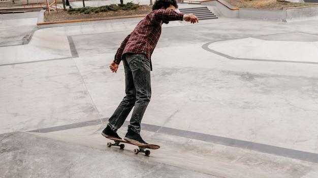 公園の外でスケートボードを楽しんでいる男