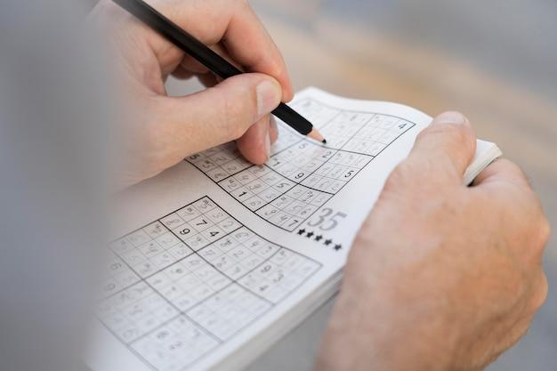 Uomo che si gode da solo un gioco di sudoku su carta