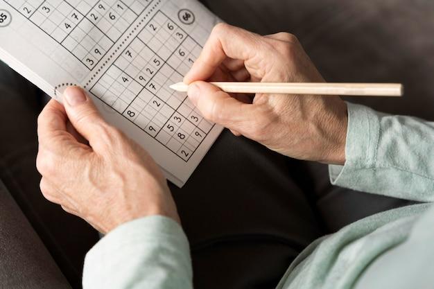 Man enjoying a sudoku game on paper by himself