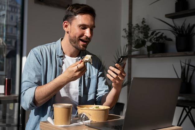Человек, наслаждающийся едой на вынос и с помощью смартфона