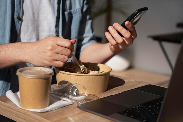 Man enjoying takeaway food and using smartphone