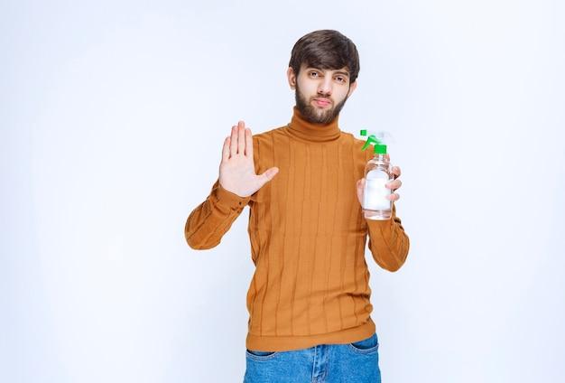 Человек, наслаждаясь новым химическим дезинфицирующим средством для рук.