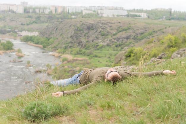 風光明媚な山の谷を見下ろす丘の上に広げて横たわって太陽を楽しむ男
