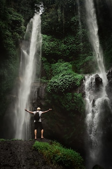 Man enjoying waterfall raised hands. travel lifestyle and success concept vacations into the wild nature on mountain and rainforest.