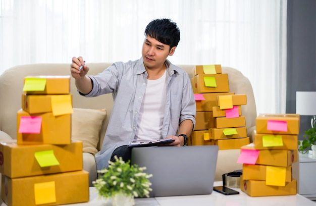 Man entrepreneur checking and writing order for delivery to customer, sme business online in home office