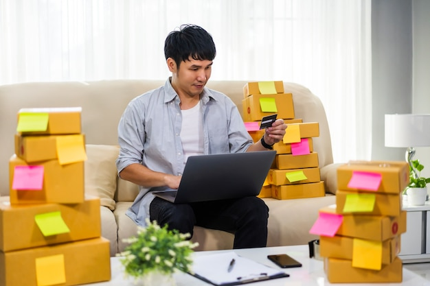 Man entrepreneur working with laptop computer and using credit card at home office