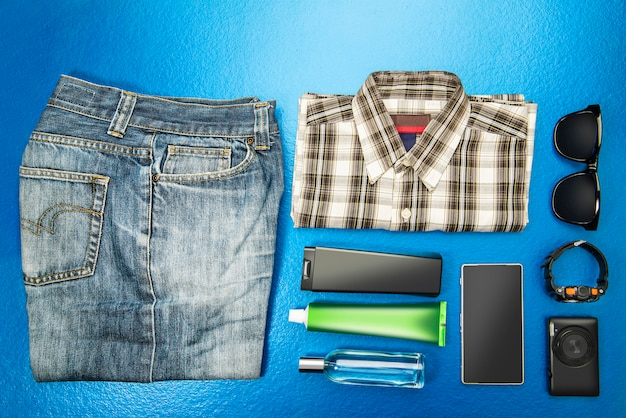 Man equipment like casual outfits with sunglasses, wristwatch, camera, mobile phone and hygiene kit for travel