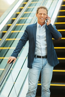 Man on escalator. confident mature man in moving down by escalator and talking on the mobile phone
