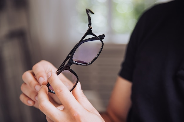 Man examines the material of the rim of stylish eyeglasses