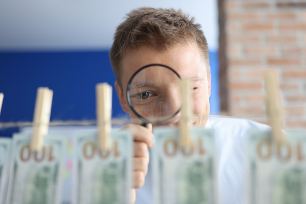 男は虫眼鏡を通してお金を調べます