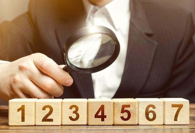 남자는 돋보기로 번호가 매겨진 블록을 검사합니다.