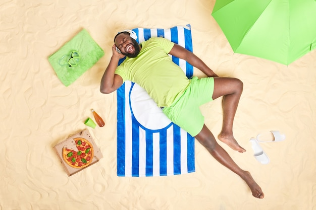 Man exclaims loudly enjoys listening music via headphones wears green t shirt and shorts eats tasty snack lies on striped towel poes at beach.