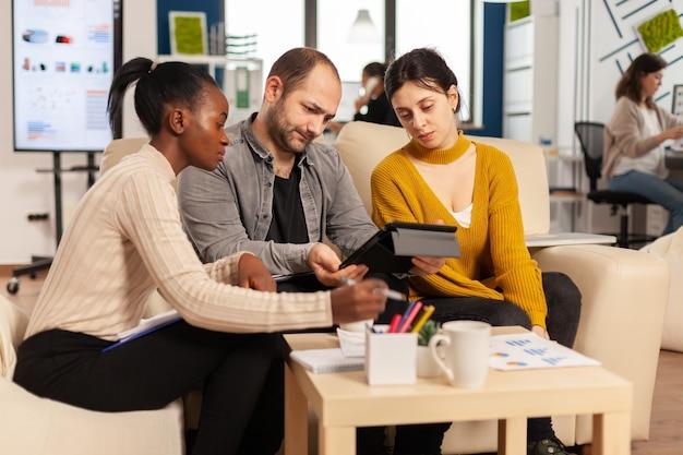 Uomo dirigente che istruisce diversi dipendenti nella nuova moderna stanza dell'ufficio aziendale prima di un incontro di lavoro con i partner che analizzano i rapporti sul tablet reports