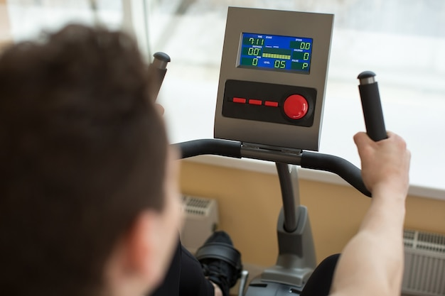 Man on exercise bike in gym