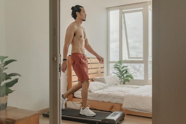 彼のアパートのトレッドミルの上を歩くことによる男の運動