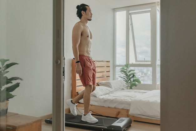 Man exercise by walking on the treadmill in his apartment