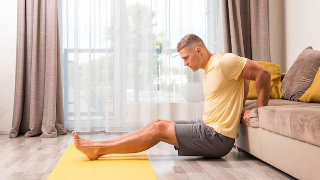 ソファを使用して自宅で運動する男性