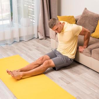 Человек, тренирующийся дома, используя диван