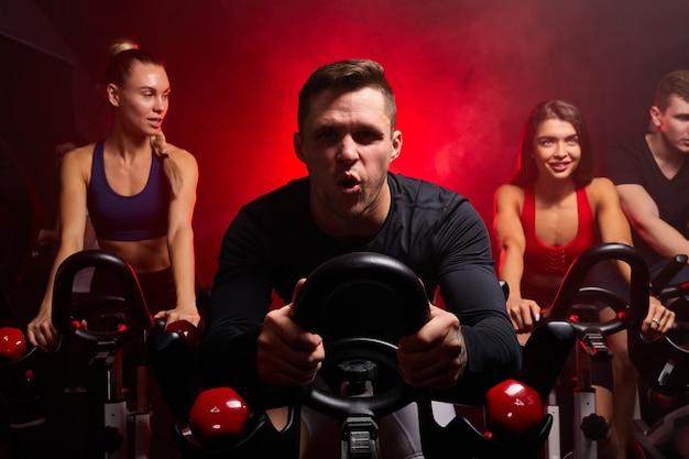 壁に友達とフィットネスジムで自転車で有酸素運動をしている男性。ボディービルダー、ライフスタイル、エクササイズフィットネス、トレーニング、スポーツトレーニングのコンセプト