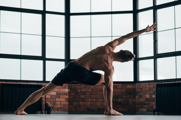 Man exercising downward dog asana in gym.